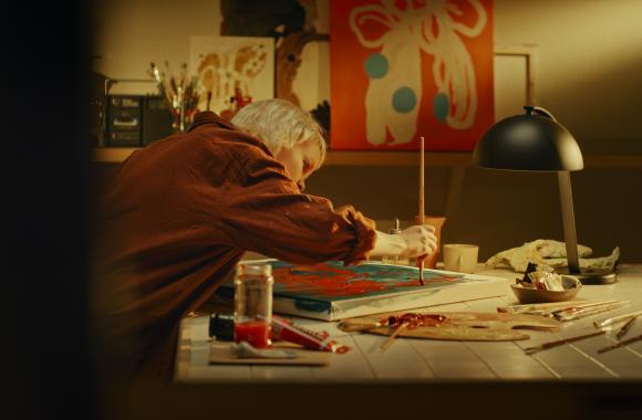 Taiteilija maalaa taulua punaisella maalilla